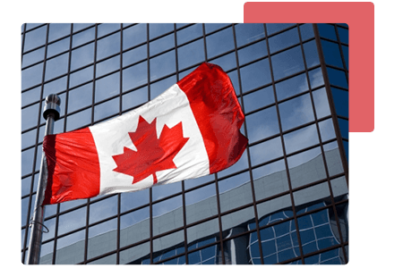 close up of Canadian flag flying in front of an office skyscraper with wall to wall glass windows