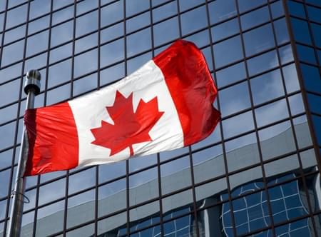 canadian flag flying on flag pole in front of sky scraper office building with wall to wall glass windows