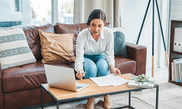 woman sitting on leather couch wearing headset while typing on laptop and looking at papers.