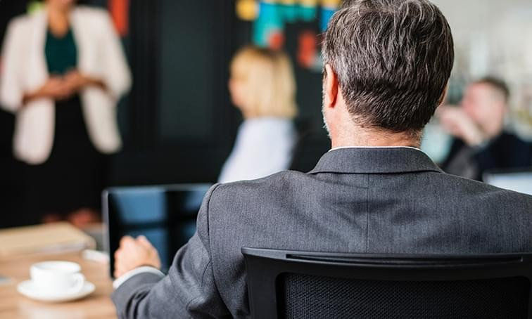 man in a meeting on his computer