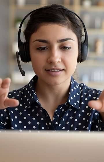 woman wearing a headset on a laptop video call gesturing forward and upward with both hands