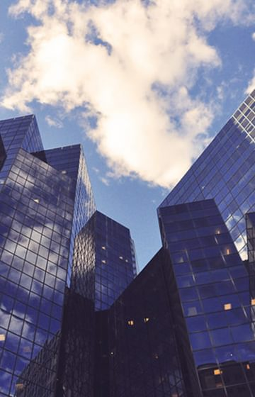 Glass Office Buildings Downtown Blue Sky with Clouds - net2phone Canada - Business VoIP Phone System