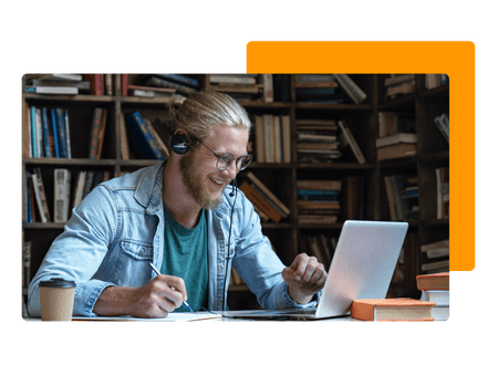 man sitting at desk wearing headset laughing while writing notes and looking at laptop with full bookshelf in background