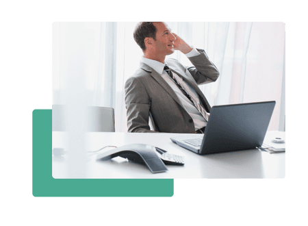 man in suit sitting at desk talking on phone in front of conference phone and laptop - net2phone Canada - Business VoIP Phone System