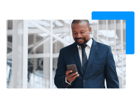 man in suit standing in front of modern office smiling while looking at smart phone