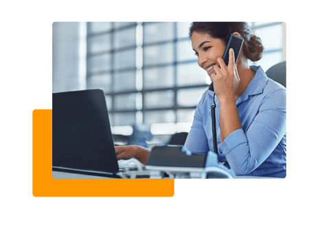 Woman in office talking on phone and typing on laptop - net2phone Canada - Business VoIP Phone System