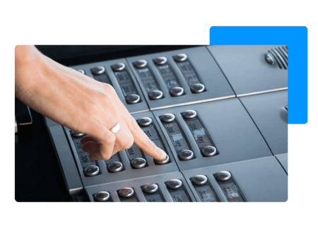 hand pressing buttons on paging phone system - net2phone Canada - Business VoIP Phone System