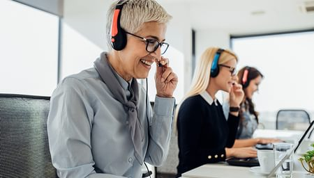 three women in business attire with headsets working in a call centre seated in front of laptops