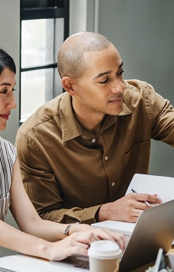new employee welcome pack man and woman work together on laptops