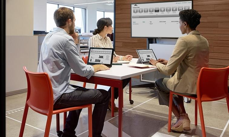 people sitting at a desk looking at a dashboard