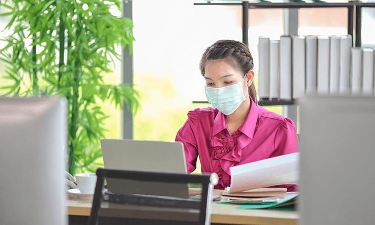 an image of a woman wearing a mask at her desk
