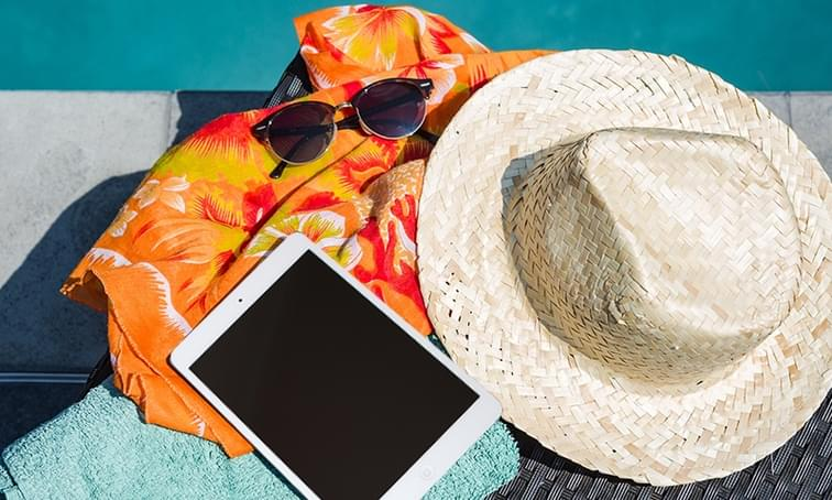 hat, ipad, towel and sunglasses at the beach