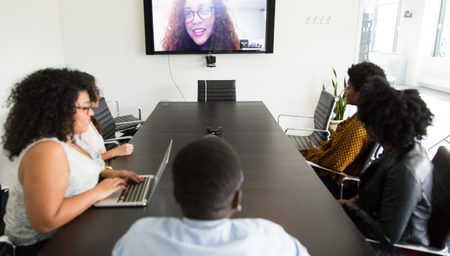 employees around a boardroom table speaking to a woman on a video call - net2phone Canada - Business VoIP Phone System