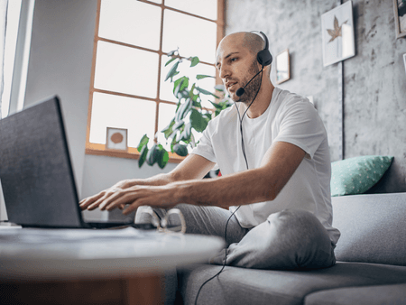 man wearing a headset and typing on a laptop working from home on his couch