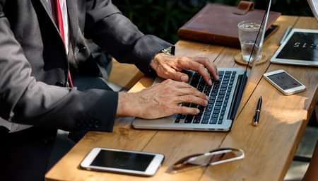 Man using laptop on wooden desk with cellphone and glasses on table - net2phone Canada - Business VoIP Phone System