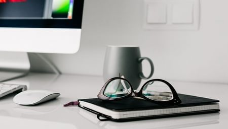 Eye Care pros - glasses on notebook on desk with apple desktop - net2phone Canada - Business VoIP Phone System