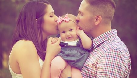 Couple kissing baby outdoors - Lane Insurance - net2phone Canada - Business VoIP Phone System