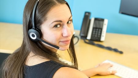 Brunette woman wearing phone headset looking at camera - net2phone Canada - Business VoIP Phone System