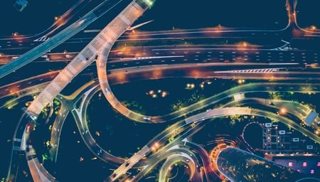 aerial time-lapse night traffic on a busy city highway interchange