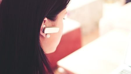 Ear set bluetooth worn by brunette woman - net2phone Canada - Business VoIP Phone System
