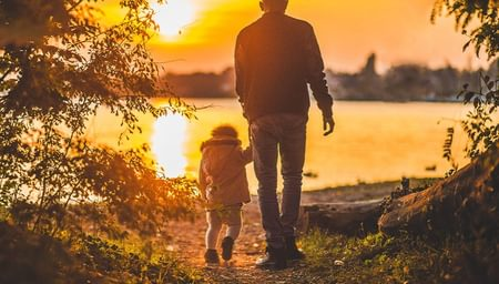 Man holding a childs hand overlooking a lake at sunset - net2phone Canada - Business VoIP Phone System