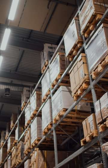 warehouse aisle with boxes stacked on metal racks