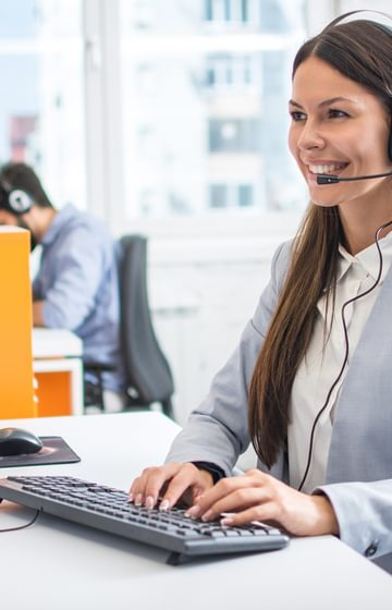 Smiling woman wearing phone headset on desktop computer - net2phone Canada - Business VoIP Phone System