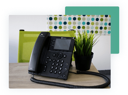 Poly phone on wooden desk next to a plant - net2phone Canada - Business VoIP Phone System