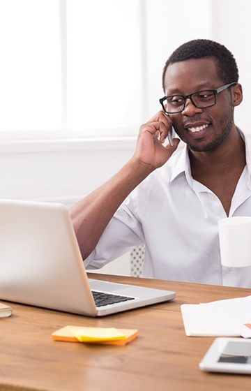 A man at his desk on the phone in front of his laptop at home