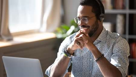 man with headset on smiling while seated in front of laptop in home office