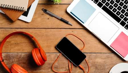 headphones, a phone, a pen, notebooks, and a laptop on a desk