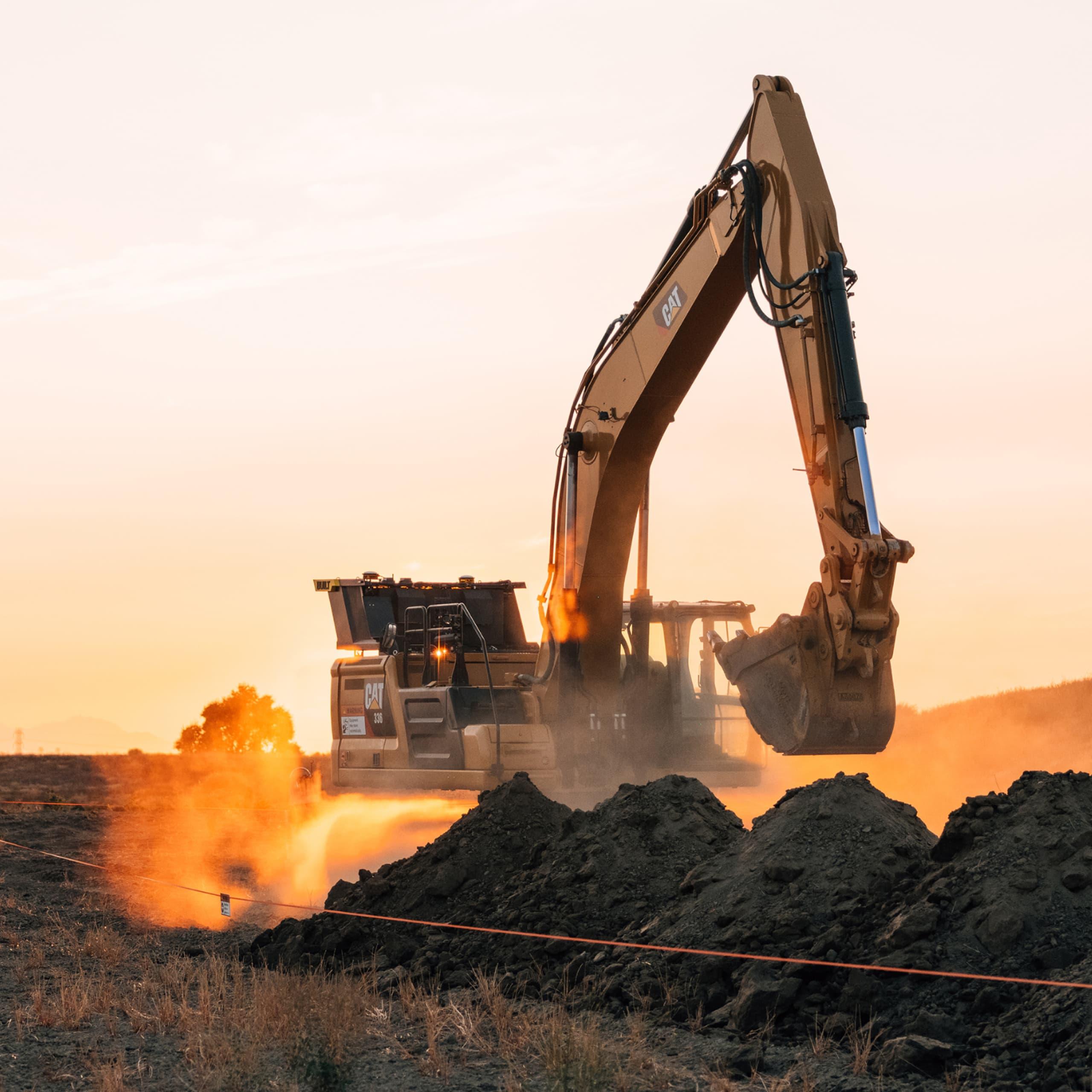 Excavator digging dust sunset