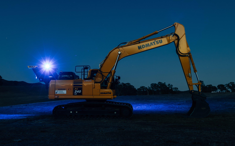 Nighttime beaming light on excavator