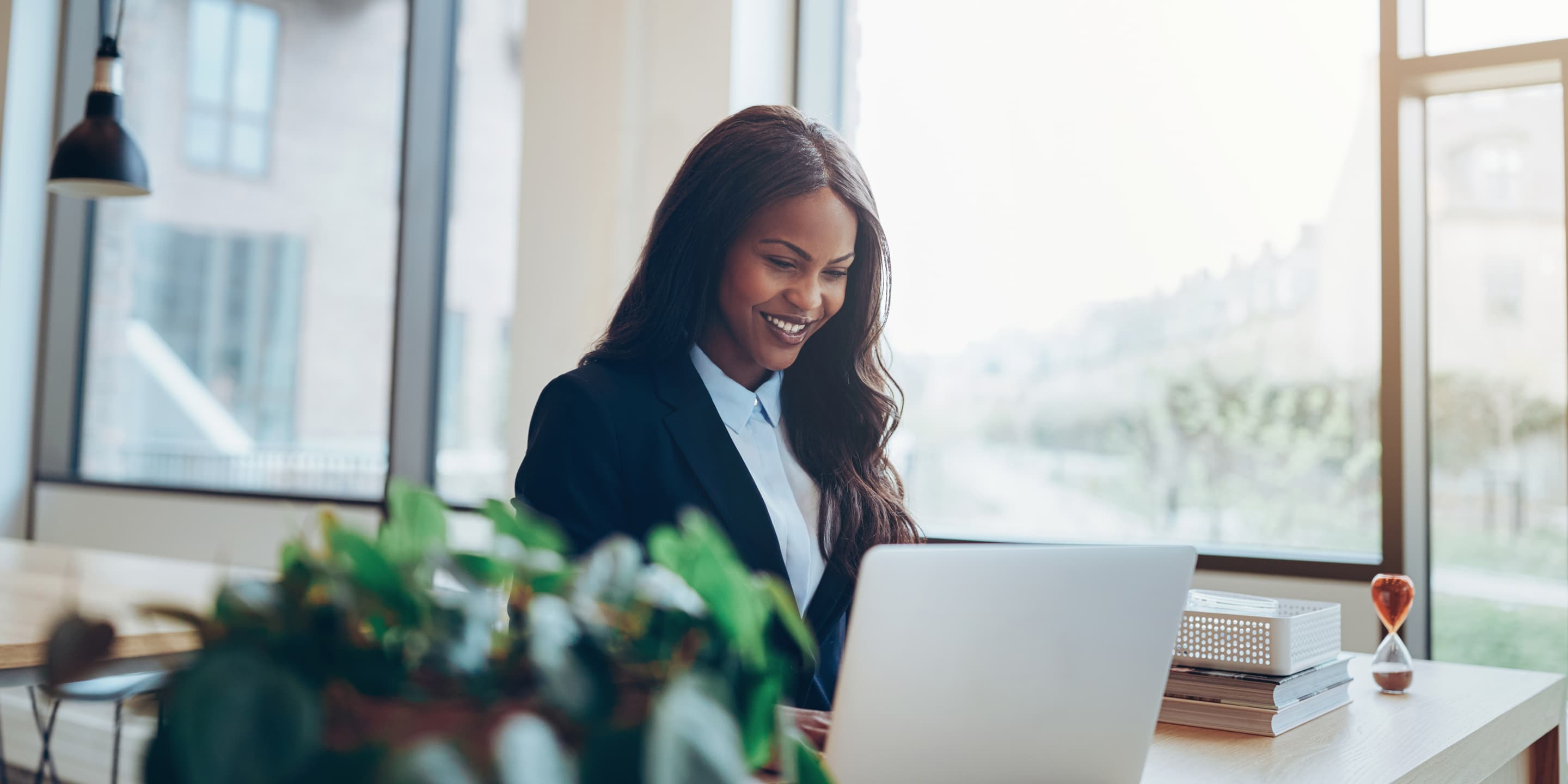 Smiling african american businesswoman using a lap LXD7 WJG
