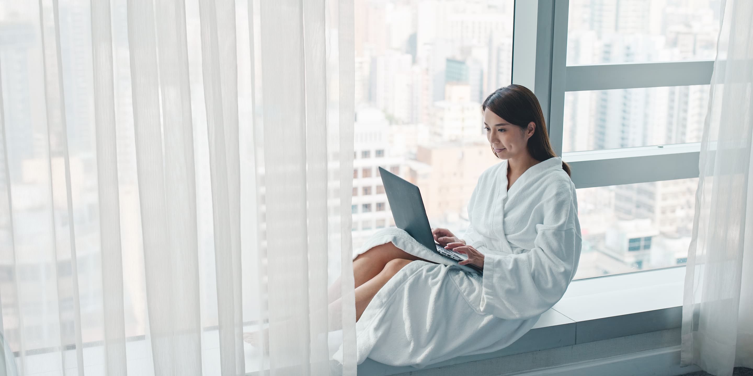 Woman work on laptop computer in hotel room CSSLVXY