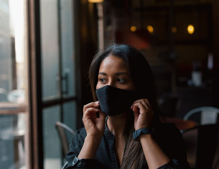 Young woman putting on face mask in coffee shop 3 P2 VMHP
