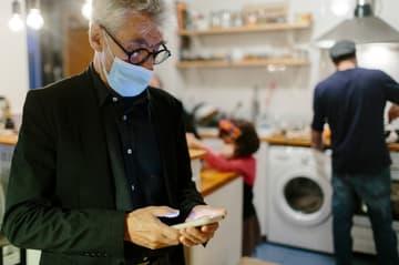 Chef in der Küche Maske und Smartphone
