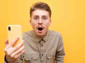 Mann mit roten Haaren, Brille und Schnurrbart hält gelbes Smartphone ist entsetzt