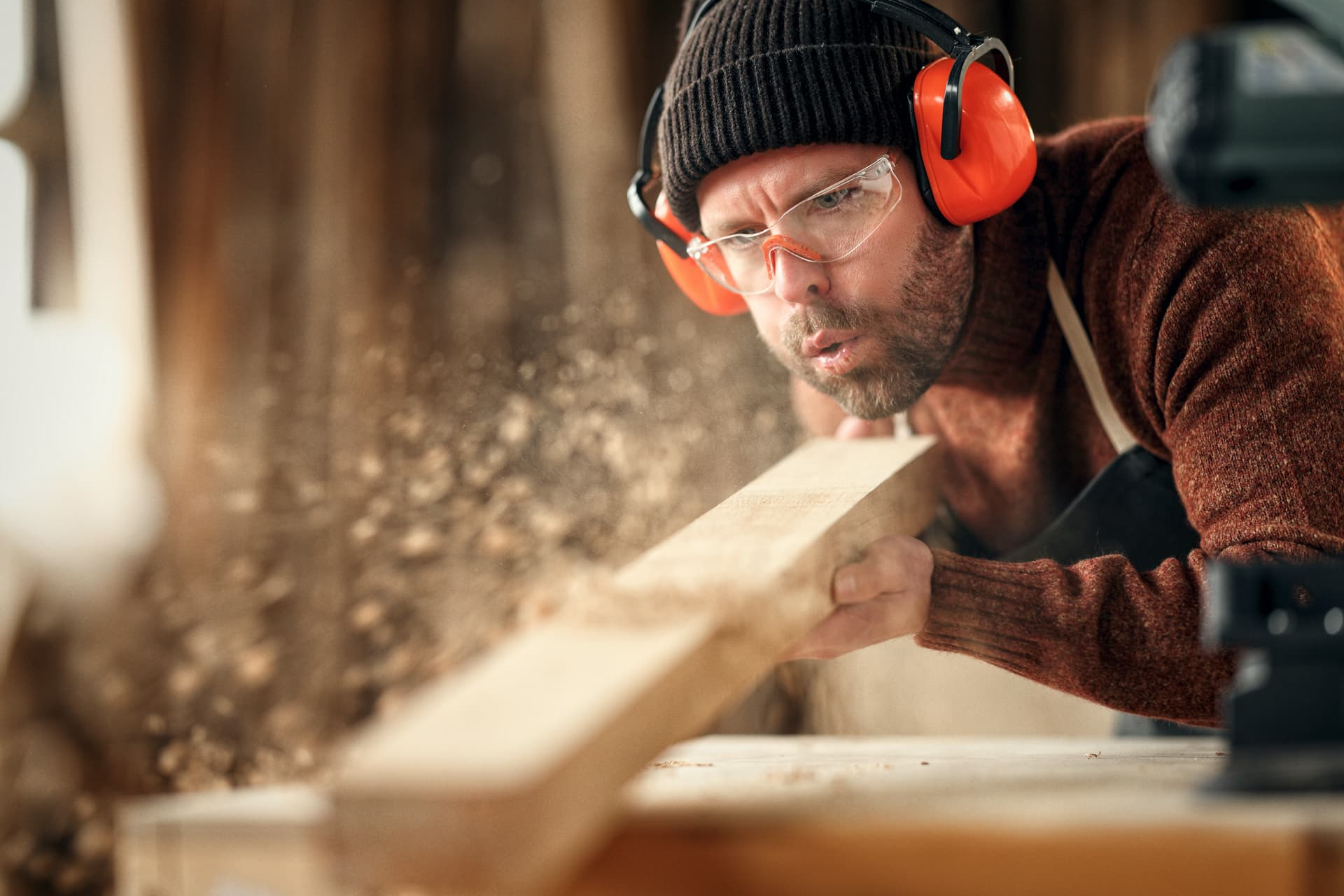 Handwerker Schreiner pustet Holzspäne
