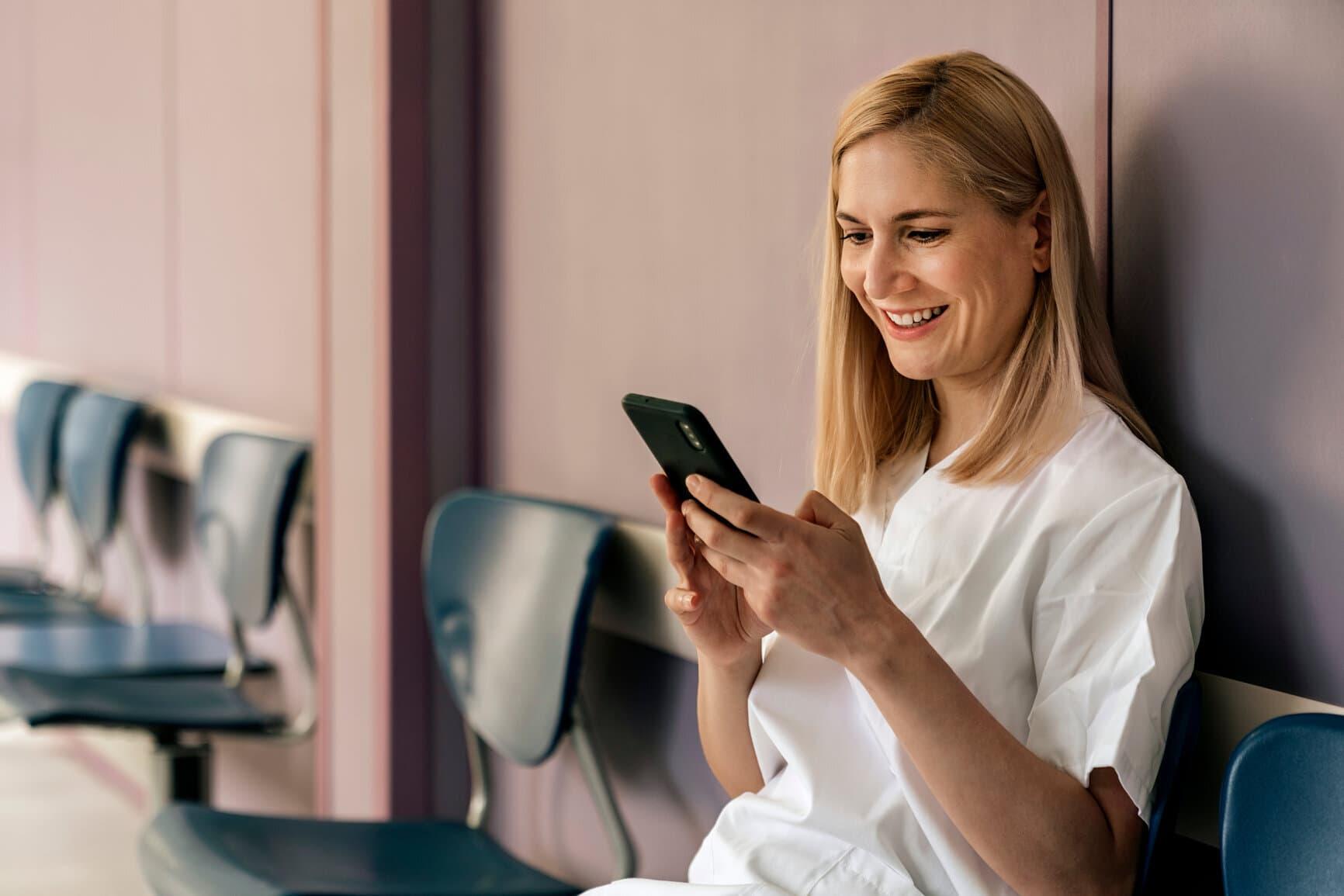 Krankenschwester mittelalt sitzend smartphone Mitarbeiter-App