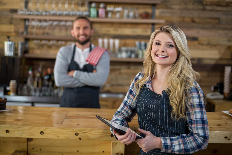 Kellnerin und Barkeeper in Restaurant mit Tablet