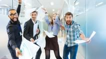Group of joyful excited business people throwing papers and having fun in office