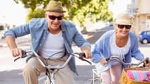 Happy mature couple going for a bike ride in the city on a sunny day 1