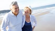 Senior couple walking on the beach in fall season 1