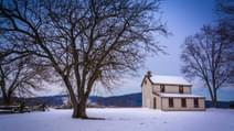 Small house and trees in a snow covered field in Gettysburg Pennsylvania