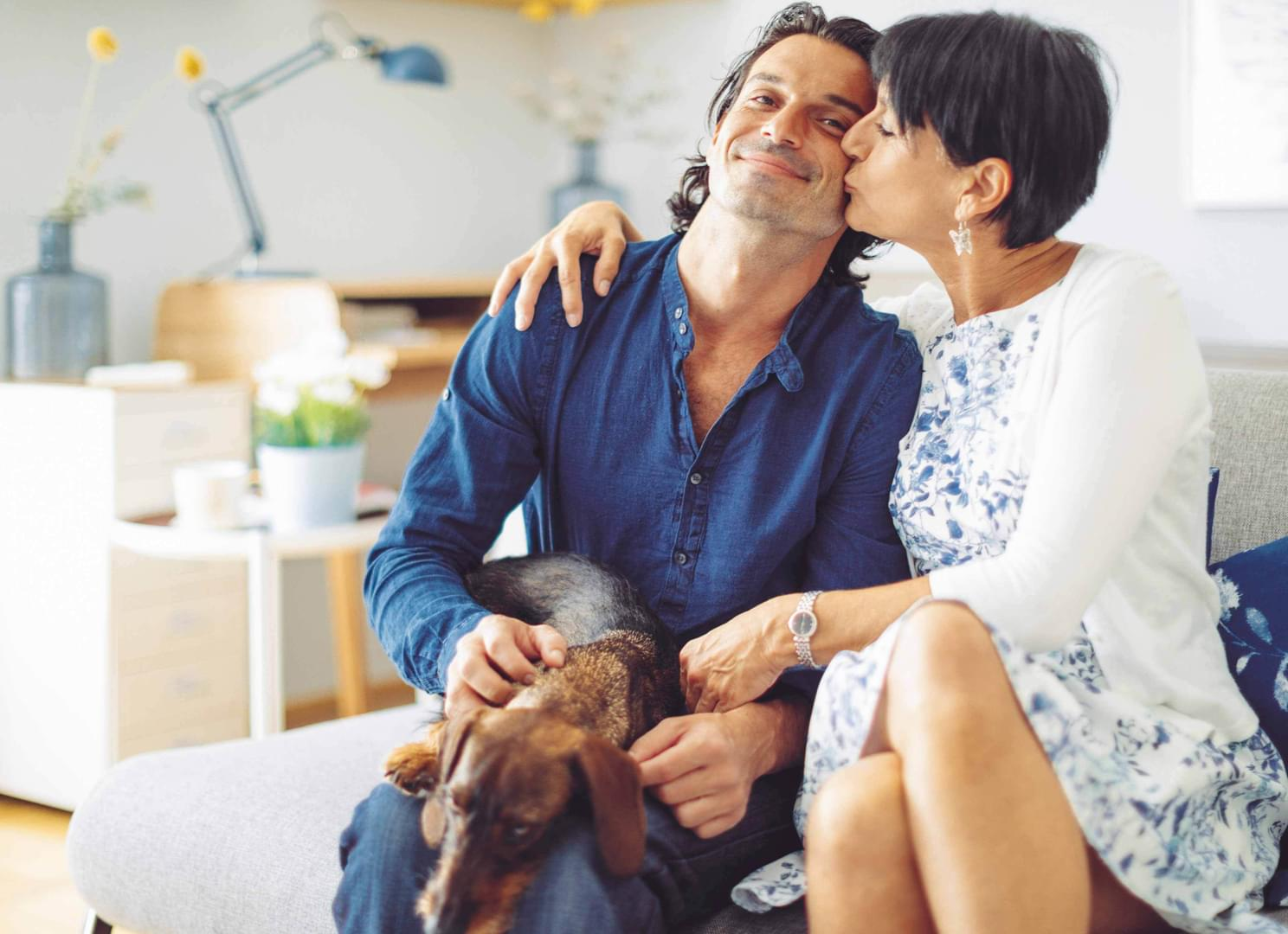 A happy couple confidently sit on their couch with their dog.