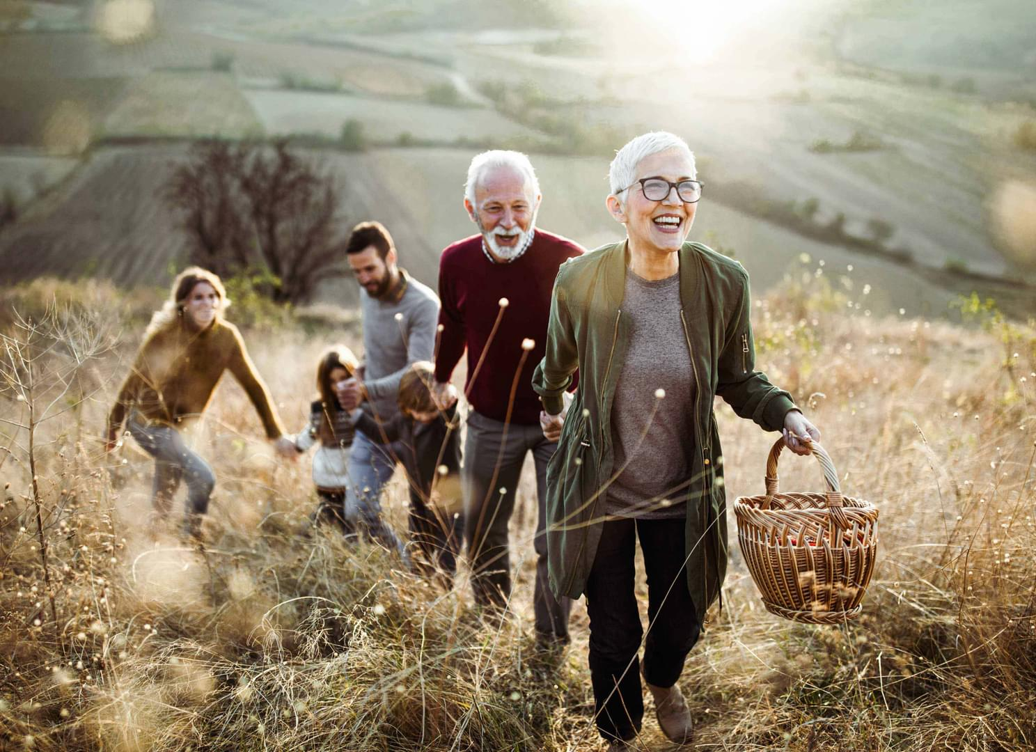 An older couple is hiking on a hillside along with their son and his family.