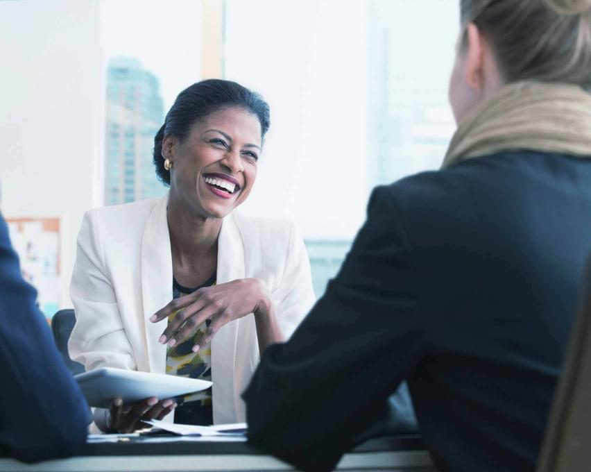 A women smiling in an office, meeting with a client.