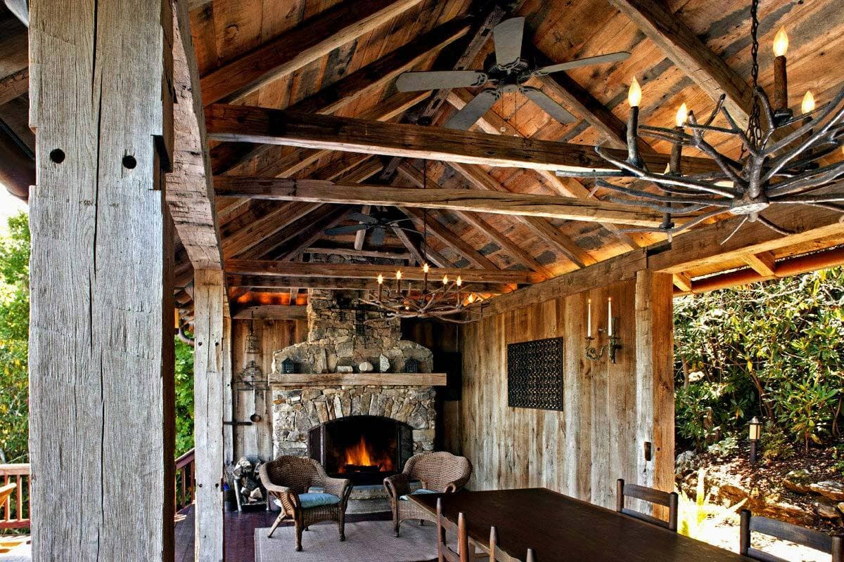 Rustic reclaimed hand hewn beams in outdoor dining room.