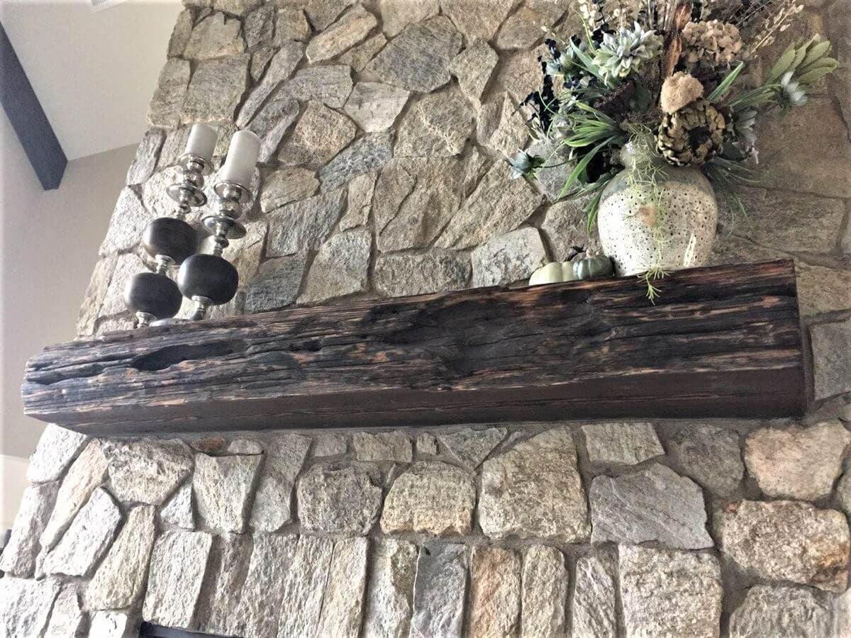 Shou sugi ban floating wood mantel on stone fireplace.